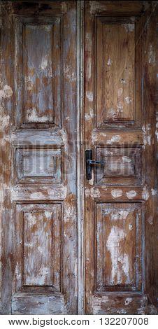 brown old door with cracked paint and iron door handle