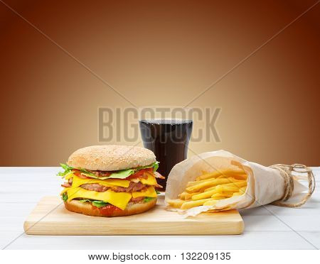 Fast food. Hamburger, potato fries, cola drink. Takeaway food. Wrapped French fries, Cola glass, double cheese hamburger or cheeseburger at white wood and brown background. American burger food