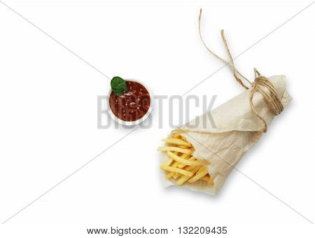 Potato french fries wrapped in brown wrapping paper. Fast food take away at white shabby chic wood. Fried potatoes with tomato sauce. Chips, potato slices. Top view with copyspace