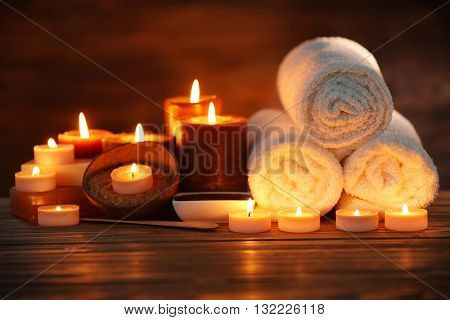 Spa composition with candles on brown background