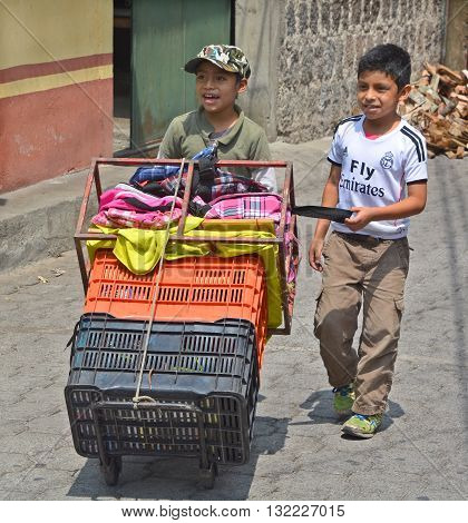 SANTIAGO DE ATITLAN GUATEMALA APRIL 29 2016: Portrait of maya boys carring merchandises. The Mayan people still make up a majority of the population in Guatemala,