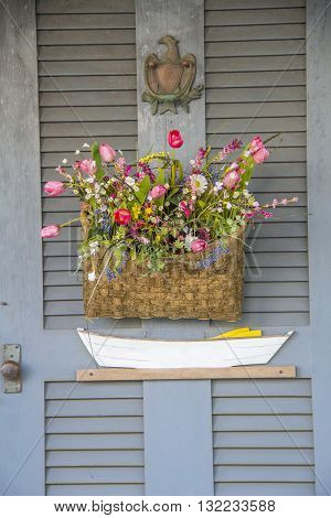 Quaint New England Door - Rustic gray door with a flower basket and Dory Boat, with a brass eagle door knocker