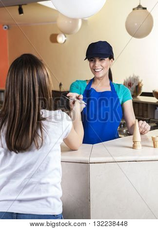 Girl Giving Dollar Note To Waitress In Ice Cream Parlor
