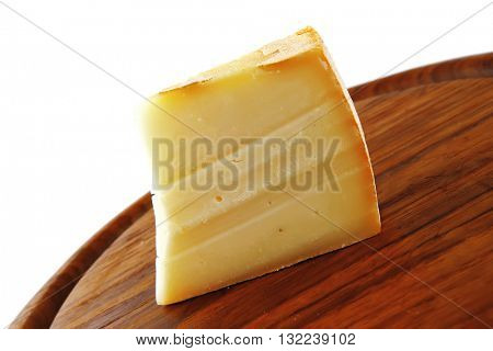 piece of light edam cheese on wooden board