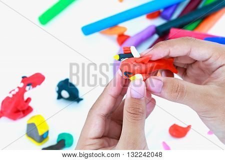 Close up. Child playing and creating toys from play dough. Child molding model clay. Strengthen the imagination of child. poster