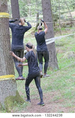 STOCKHOLM SWEDEN - MAY 14 2016: Three woman with mud in their face trying to maintain the balance on a slack rope in the obstacle race Tough Viking Event in Sweden April 14 2016