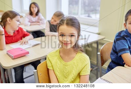 education, elementary school, learning, children and people concept - student girl with group of classmates in classroom