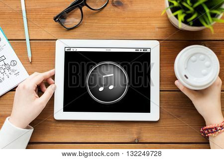 technology, people and multimedia concept - close up of woman with music media player icon tablet pc computer screen and coffee on wooden table