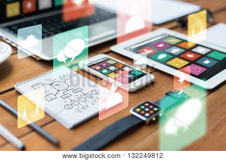 business, responsive design and technology concept - close up of laptop computer, tablet pc, notebook and smartphone with scheme and menu icons on wooden table