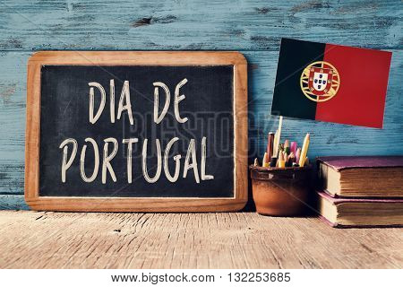 the text Dia de Portugal, Day of Portugal written in Portuguese in a chalkboard, and a flag of Portugal, on a rustic wooden table