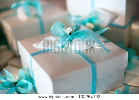 Decorative gift-wrapped party favor in a box tied with a turquoise blue ribbon and bow for a catered celebration or festive party