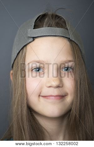 portrait of child girl with long hair in hooligan style cap