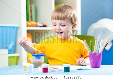 Little Boy painting in kindergarten or daycare center
