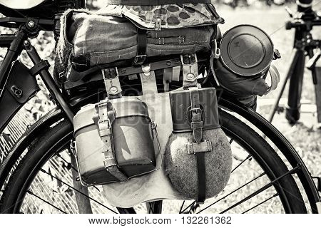 Close up photo of old military bicycle with equipment. Backpack and containers for food and drink. Vintage scene. Black and white photo. Retro transport. Equipment of german soldier in World War II.
