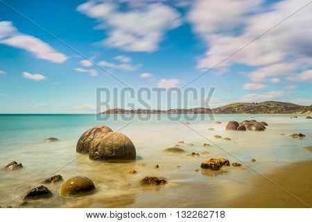 Long exposure image of Moeraki Boulders lying along a stretch of Koekohe Beach on the wave-cut Otago coast of South Island New Zealand. These formations are a major tourist attraction of the area.