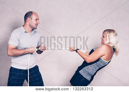 Man and determined sporty woman pulling a rope. Competition determination and effort concept.