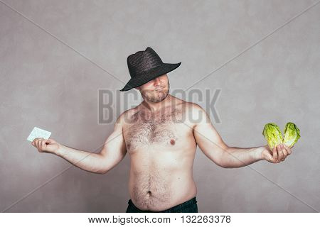 Indecisive naked corpulent man in hat holding pharmaceutical products and lettuce.