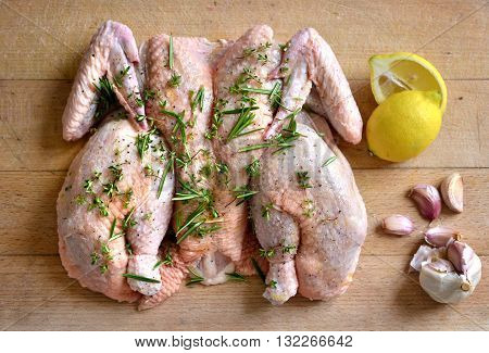 Raw spatchcock chicken with garlic herbs and lemon