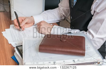 Consultant or adviser is writing in office.