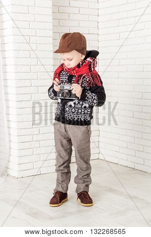 Little boy with retro camera in hand. Closeup