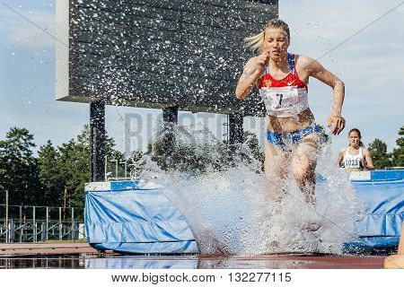 Chelyabinsk Russia - May 24 2016: female athletes leader of race at steeplechase during UrFO Championship in athletics