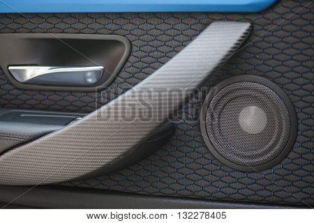 Close up shot of a round speaker in a car.