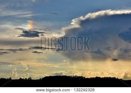 Parhelion (sundog) next to a thundercloud atmospheric phenomenon created by light interacting with ice crystals