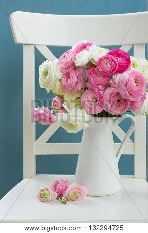 Pink and white ranunculus flowers in vase on chair