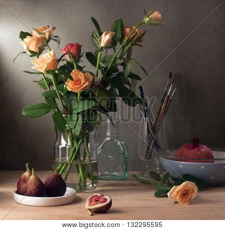 Still life with roses and figs over wooden table