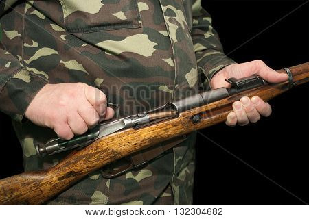 Hunter in camouflage clothing holding an old rifle and a cartridge in the chamber shall be sent on a black background