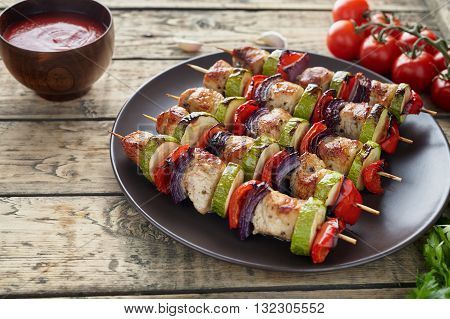 Chicken or turkey meat shish kebab skewerrs with onion tomatoes and ketchup in clay dish on rustic wooden background. Traditional barbecue grill food