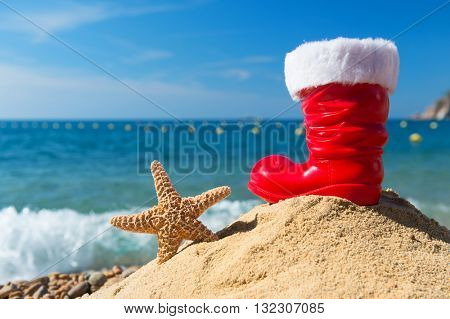 Funny starfish and red boot from Santa Claus at the beach for Christmas