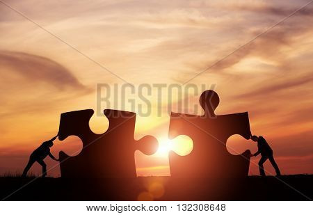 Teamwork concept. Two businessman connecting puzzle pieces togheter with copy space