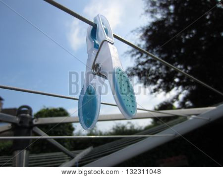 A blue clothes pin hanging on the clothes line.