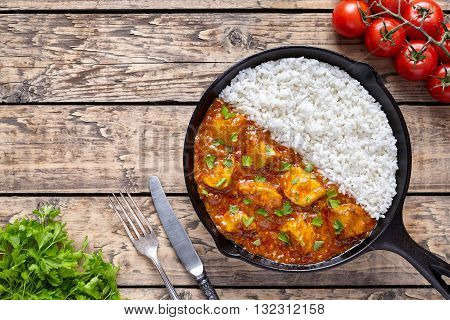 Chicken tikka masala Asian traditional spicy meat food and rice in cast iron skillet with tomatoes, butter, knife. fork and parsley on vintage wooden background. Karahi chicken or korma vindaloo