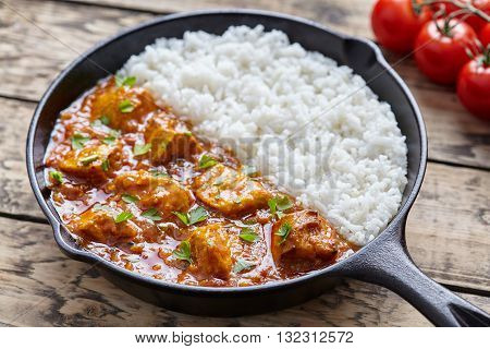 Tikka masala traditional Indian butter chicken spicy meat food and rice with tomatoes in cast iron skillet on vintage wooden background. Karahi chicken recipe