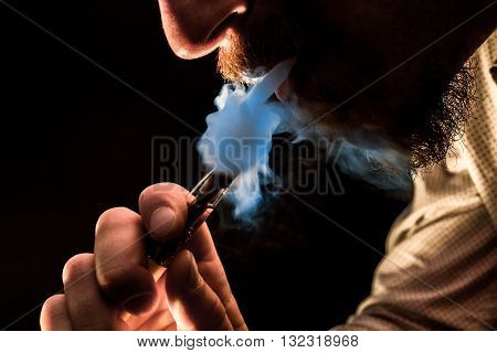 Dramatic lighting bearded man smokes a vape e-cigarette