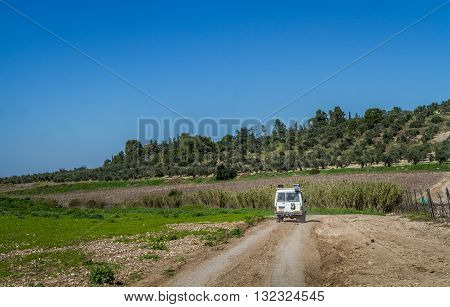 SUV rides on the country road among meadows in Neve Shalom Israel