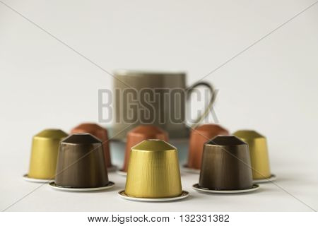 Selection of coffee pods with out of focus espresso cup on white background