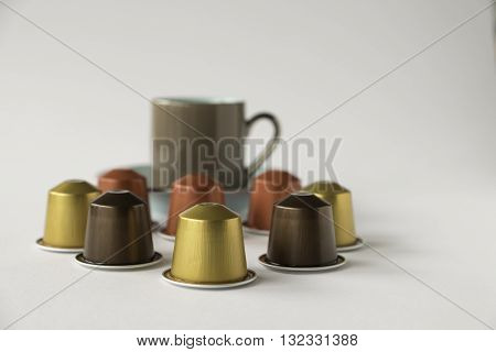 Variety of coffee pods with out of focus espresso cup against white background