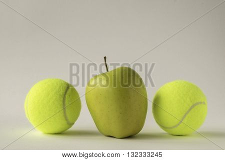 Odd one out - shiny yellow apple between two tennis balls against white background