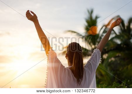 Back view of blissful woman at tropical beach enjoying relax freedom and vacation. Female raising arms towards the sun on beautiful sunrise. Summer happiness and leisure.