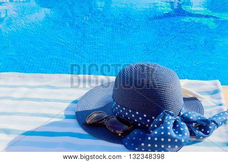 towel and summer hat near blue clear water of pool