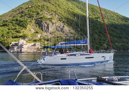 Tivat, Montenegro - 26 April, Sailboat without sails pass by the scenic shores, 26 April, 2016. Regatta