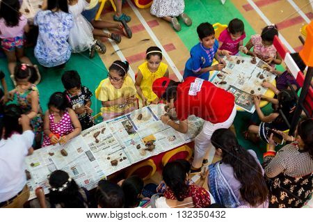Delhi, India - 29th May 2016: Group of children being taught clay modelling by a teacher at a shopping mall in India. Summer classes are very popular to develop hobbies and art in the child