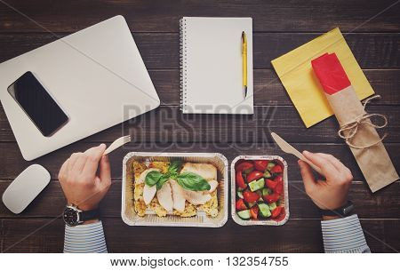 Business lunch at working place. Businessman in office. Healthy, diet food take away in aluminium boxes: roasted turkey with salad. Cell phone, mobile, fitness bracelet on hand. Top view, flat lay