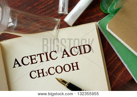 Word acetic acid written on a page. Chemistry concept.