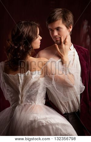 Portrait of the elegant young couple in medieval era costumes. Book cover poster