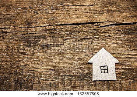 Cardboard house on a wooden background. Building wooden houses