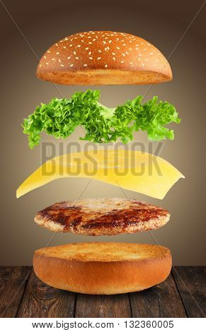 Burger ingredients. Burger layers isolated. Separated burger ingredients on wood. Hamburger explosion. Cheeseburger flying layers on brown background. Levitation of burger and cheese, meat, lettuce.
